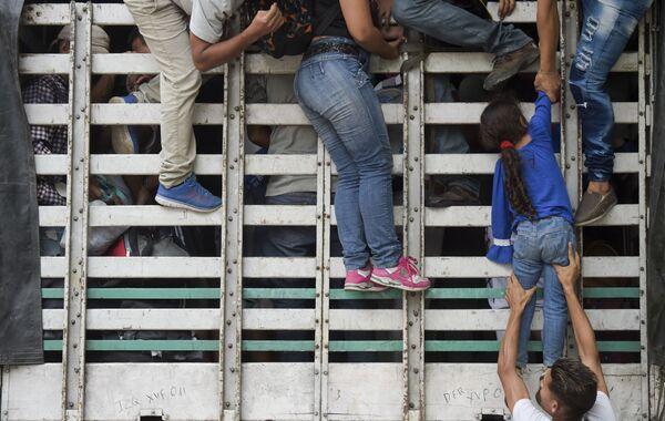 Мигранты из Венесуэлы забираются в грузовик по дороге из Кукуты в Памплону, Колумбия