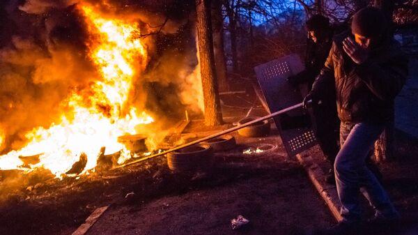 Сторонники оппозиции подбрасывают шины в огонь на баррикаде в Киеве