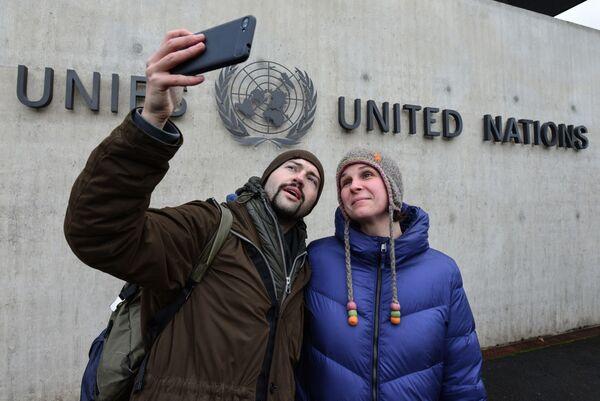 Туристы фотографируются на фоне здания Организации Объединённых Наций (ООН) в Женеве