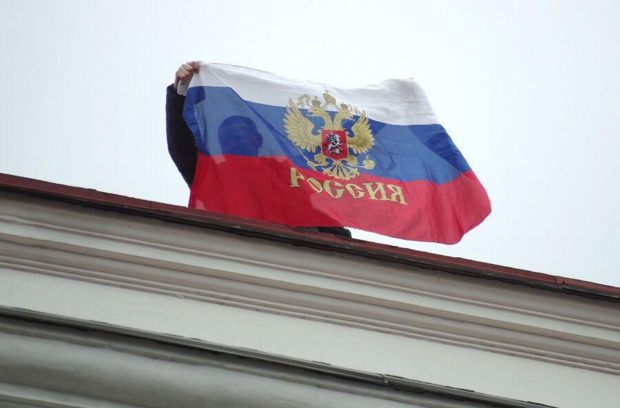 Местный житель с российским флагом на крыше Горсовета в Севастополе