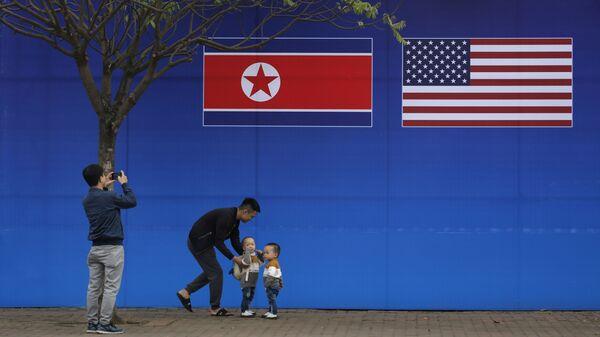 Люди фотографируются на фоне плаката к саммиту между США и Северной Кореей в Ханой, Вьетнам