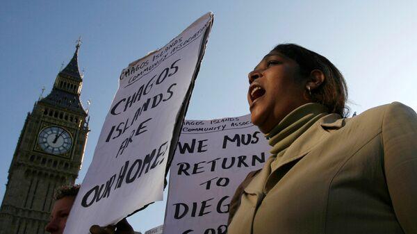 Демонстрант с требованием возвращения острова Чагос архипелага Диего-Гарсия во время акции протеста перед зданием парламента в Лондоне. 22 октября 2008