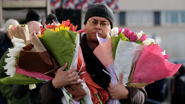 Мужчина с цветами на Рижском рынке в Москве