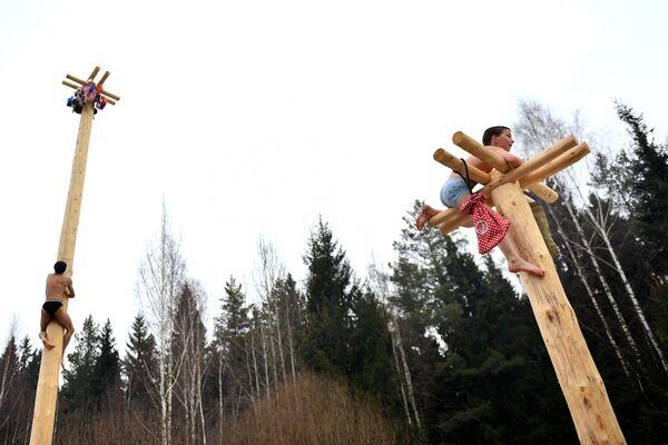 Участники старинной русской народной забавы масленичный столб во время празднования Бакшевской Масленицы в Истринском районе Московской области