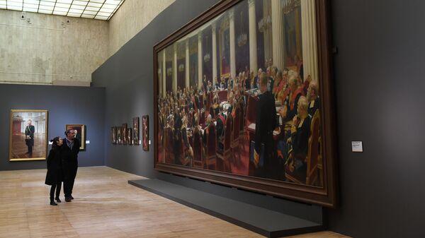 Посетители возле картины Торжественное заседание Государственного совета 7 мая 1901 года в день столетнего юбилея со дня его учреждения на выставке Ильи Репина в Третьяковской галерее на Крымском валу