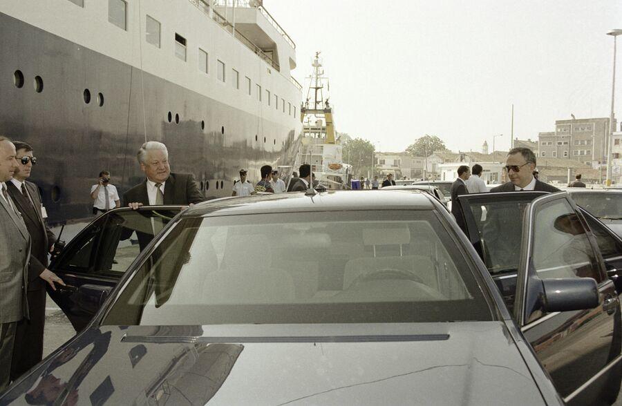 Президент России Борис Ельцин и министр иностранных дел Андрей Козырев садятся в машину в порту Греции. 11 июня 1994