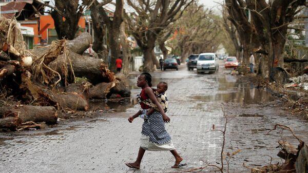Женщина с ребенком на спине пересекает улицу после циклона Идаи в Бейре, Мозамбик