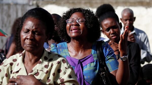 Прихожане молятся на улице после того, как их церковь была разрушена циклоном Идаи в Бейре, Мозамбик. 24 марта 2019