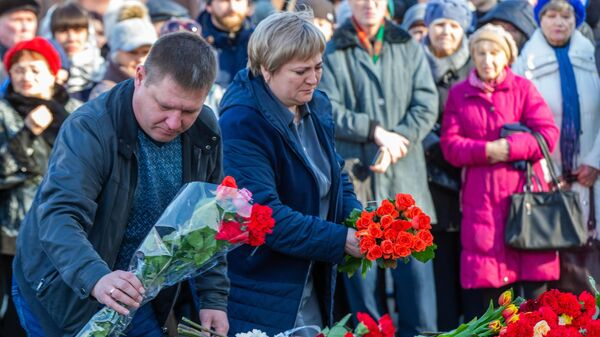 Люди возлагают цветы к мемориалу в память о жертвах пожара в торгово-развлекательном центре Зимняя вишня в Кемерово