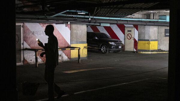 Отключение элеМужчина на автомобильной стоянке во время отключения электроэнергии в Каракасетричества в Каракасе. 25 марта 2019