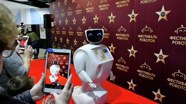 Посетители фотографируют интерактивного мобильного робота на колесной платформе Василия на фестивале роботов в Краснодаре