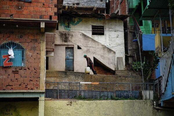 Мужчина несет воду к своему дому в районе Петаре в Каракасе