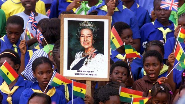 Школьники держат портрет британской королевы Елизаветы II в столице Ганы Аккре