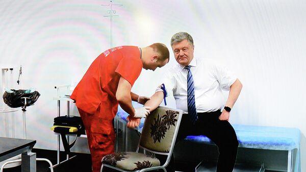 Президент Украины Петр Порошенко на экране монитора во время трансляции сдачи анализа крови на алкоголь и наркотики в антидопинговом центре НСК Олимпийский в Киеве