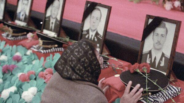 Женщина плачет у портрета сына. Похороны моряков подводной лодки Комсомолец