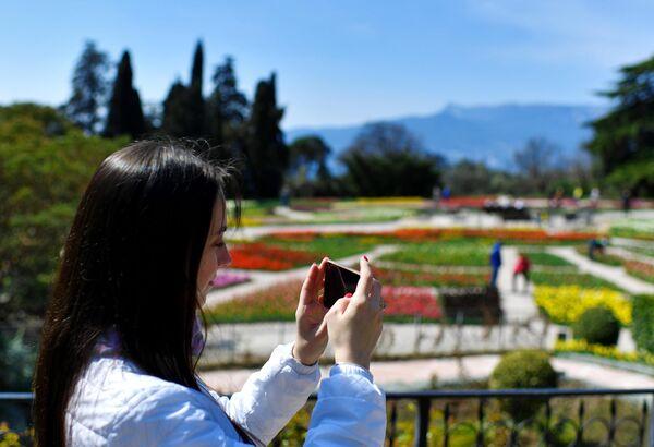 Девушка фотографирует в Никитском ботаническом саду в Крыму