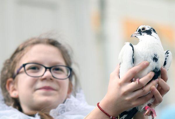 Девочка с  голубем после богослужения в праздник Благовещения Пресвятой Богородицы в Благовещенском соборе Московского Кремля
