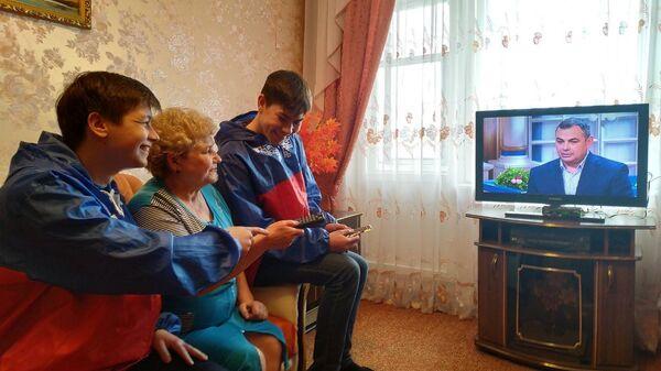 Никита Мамонов и Данил Алешин помогают пенсионерке Галине Никулиной разобраться с пультом