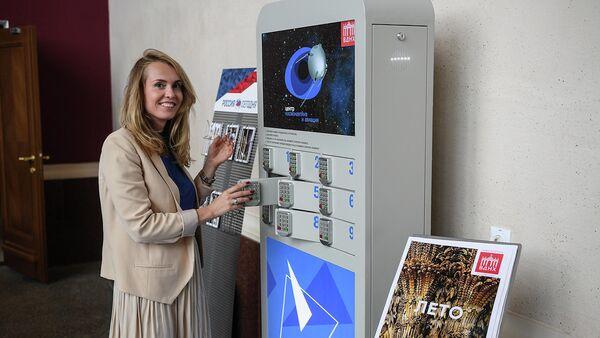 Посетитель Центра Космонавтика и авиация в павильоне Космос на ВДНХ ставит заряжать мобильный телефон в специальное устройство