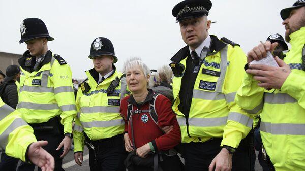Сотрудники полиции задерживают участницу акции протеста, организованной  Extinction Rebellion, против загрязнения окружающей среды, проходящей в Лондоне