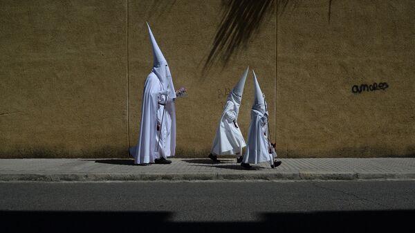 Кающиеся члены братства Ла Паз во время вербного воскресенья в Севилье