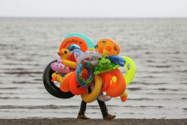 Продавец надувных кругов на берегу озера Никарагуа в Гранаде