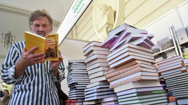 Посетитель читает книгу на книжной ярмарке во Львове