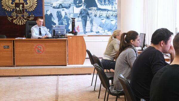 Люди сдают теоретические экзамены по правилам дорожного движения в отделении ГИБДД в Москве