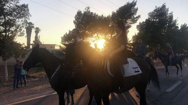 Сирийцы на лошадях едут в выставочный городок на южной окраине Дамаска