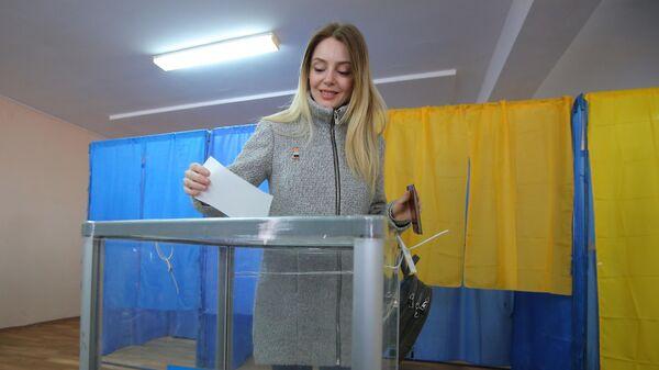 Жительница Киева во время голосования на одном из избирательных участков города в день второго тура выборов президента Украины