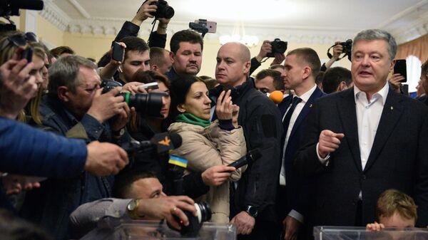 Действующий президент Украины Петр Порошенко отвечает на вопросы журналистов  во время голосования на одном из избирательных участков Киева в день второго тура выборов президента Украины