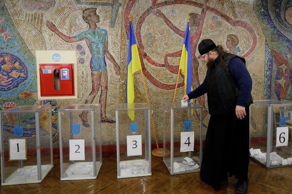 Священнослужитель во время голосования на одном из избирательных участков Киева в день второго тура выборов президента Украины