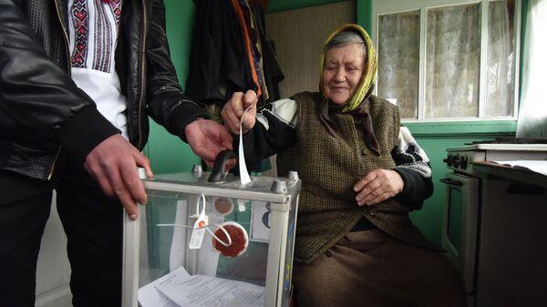 Женщина опускает бюллетень в мобильную урну для голосования во время второго тура президентских выборов на Украине