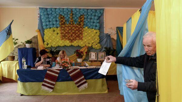 Избиратель во время голосования на одном из избирательных участков Львовской области в день второго тура выборов президента Украины