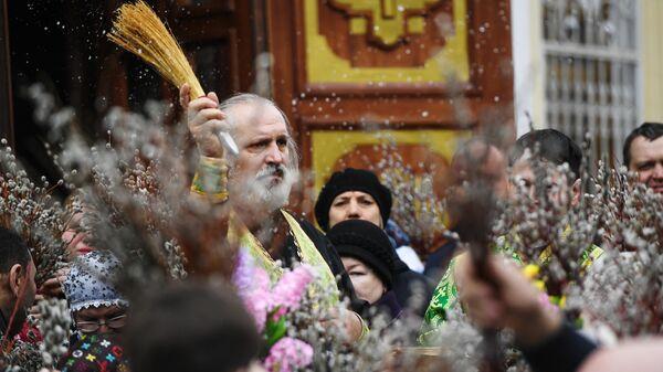 Священнослужитель и прихожане во время освящения вербы в Вознесенском кафедральном соборе в Новосибирске. 21 апреля 2019