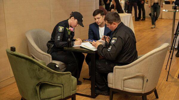 Сотрудники полиции передают протокол об административном правонарушении кандидату в президенты Владимиру Зеленскому, который публично продемонстрировал свой избирательный бюллетень при голосовании, в Киеве, Украина. 21 апреля 2019