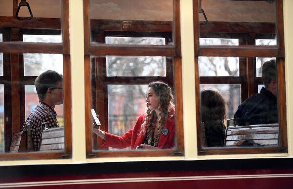 Пассажиры в трамвайном вагоне, участнике торжественного парада трамваев разных времен, на центральной улице столицы. Московский трамвай празднует 120-летний юбилей запуска трамвайного движения в столице