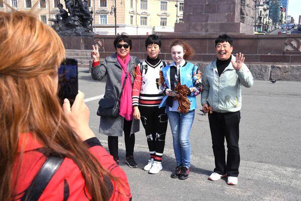 Волонтер, раздающий георгиевские ленточки во Владивостоке в рамках ежегодной акции Георгиевская ленточка, посвященной 74-й годовщине Победы в Великой Отечественной войне, фотографируется с туристами