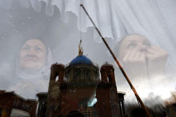 Верующие наблюдают за установкой крестов на купол Успенского собора в Екатеринбурге