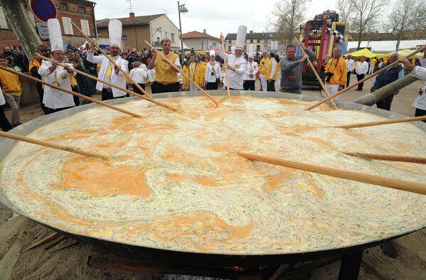 Члены братства Гигантского омлета готовят на главной площади городка Бесьер на юге Франции