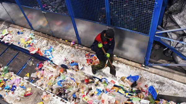 Работник поправляет мусор на конвейере завода по переработке отходов
