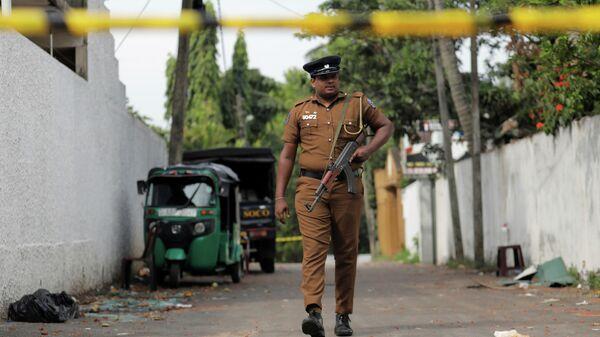 Шри-ланкийский полицейский около отеля на окраине Коломбо, где произошел взрыв. 26 апреля 2019