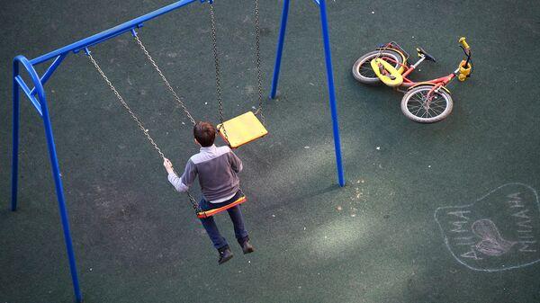 Мальчик качается на качелях на детской площадке