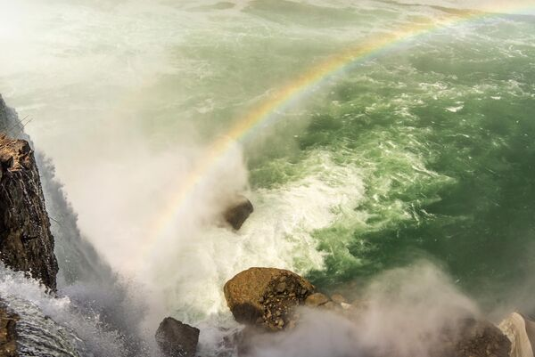 Радуга у основания Американского водопада в Государственном парке Ниагарского водопада в штате Нью Йорк, США