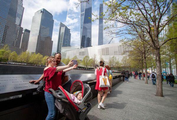 Прохожие у Национального мемориала и музея 11 сентября в Нью-Йорке