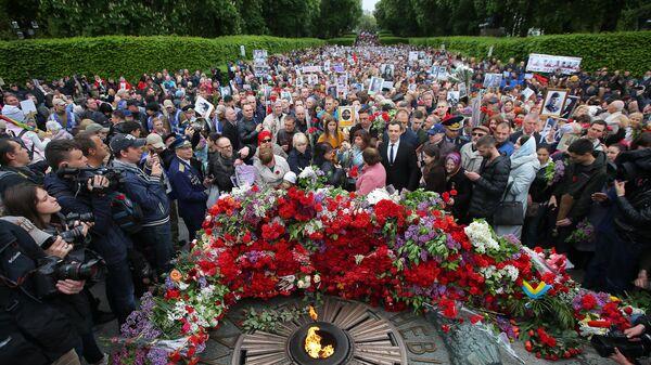 Участники акции Бессмертный полк возлагают цветы к Вечному огню в киевском парке Славы