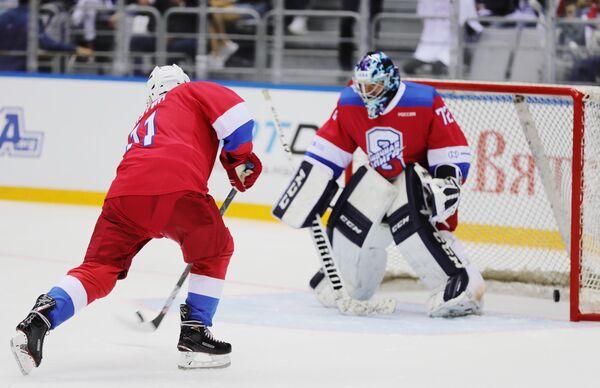 Президент РФ Владимир Путин забивает шайбу в ворота на раскатке перед началом гала-матча Ночной хоккейной лиги в ледовом дворце Большой в Сочи
