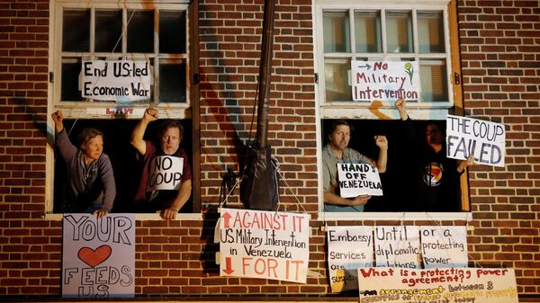 Сторонники президента Венесуэлы Николаса Мадуро в окнах здания посольства Венесуэлы в Вашингтоне.13 мая 2019