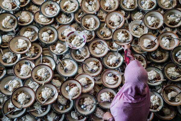 Индонезийская женщина подготавливает мусульманский ужин во время Рамадана в мечети в городе Джокьякарта