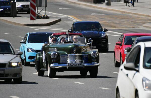 Участники в автомобиле Cadillac Sixty two Convertible 1940 года принимают участие в ралли классических ретро-автомобилей в Москве
